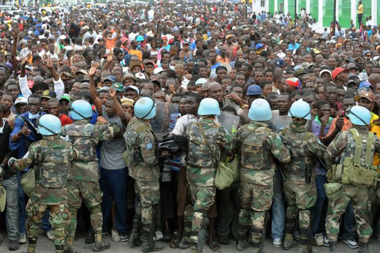 "02. United Nations ""peacekeepers"" control Haitians queueing for aid at a distribution point outside the presidential palace in Port-au-Prince on January 25, 2010."
