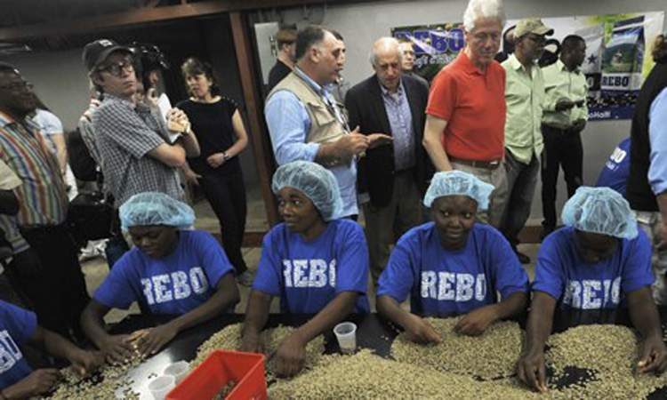 Former United States president William J. Clinton, tours a coffee processing plant in Port-au-Prince, Haiti, with an agricultural investment delegation in March 2013.