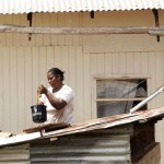 With no piped water, residents of Genus, St. Elizabeth depend on rainwater for domestic and agricultural purposes. Here, a woman harvests water from a tank into which rainwater is channeled from the roofs of two nearby buildings (photo: Ian Allen).