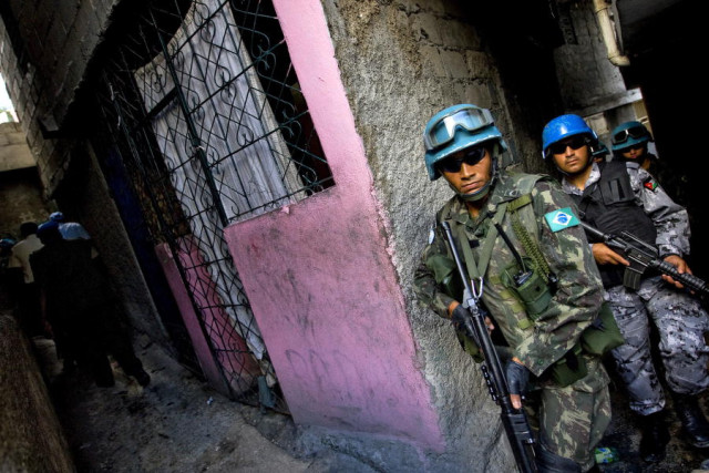 Members of the Brazilian contingent of the United Nations Stabilization Mission in Haiti (MINUSTAH) walk through an alley during a patrol of the streets of the city as part of a coordinated security programme of the military, the United Nations and the national police force during the holiday season. 18/Dec/2008. UN Photo/Marco Dormino. www.unmultimedia.org/photo/