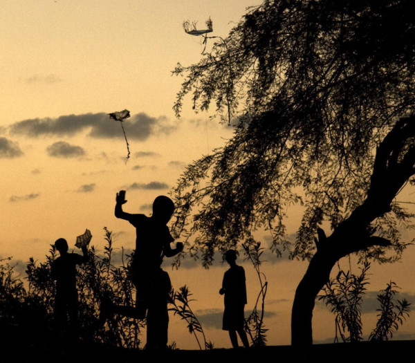 Children fly their kites at sunset inside the Petionville Club, the former Port-au-Prince golf resort now used as a sprawling campground for displaced Haitians.