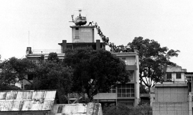 29 Apr 1975, Saigon, South Vietnam --- A CIA employee (probably O.B. Harnage) helps Vietnamese evacuees onto an Air America helicopter from the top of 22 Gia Long Street, a half mile from the U.S. Embassy. --- Image by © Bettmann/CORBIS