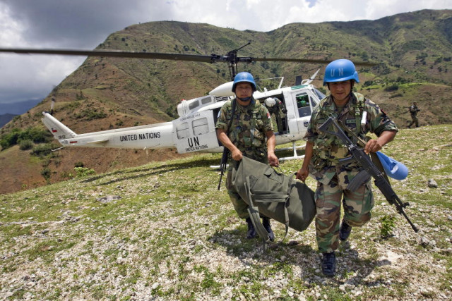 Peruvian peacekeepers from the United Nations Stabilization Mission in Haiti (MINUSTAH) unload electoral material from a UN helicopter in a mountainous region outside Port-au-Prince, Haiti for the second round of senatorial elections. The peacekeepers are tasked with providing a secure environment for the electoral process and to ensure the safety of the population and the ballots.24/Jun/2009. Port-au-Prince, Haiti. UN Photo/Logan Abassi. www.un.org/av/photo/