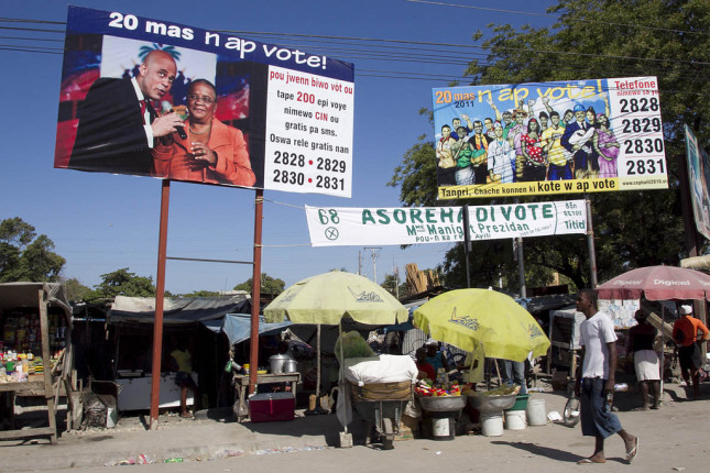 A man walks past billboards calling on people to participate in elections in Port au Prince on March 20, 2011. Haitians headed to the polls for the final round of elections. Photo Victoria Hazou UN/MINUSTAH