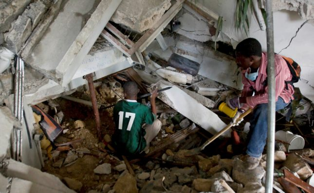 Two Haitians use crowbars, shovels and their hands to clear rubble in an attempt to reach survivors at the Montana hotel that collapsed after an earthquake measuring 7 plus on the Richter scale rocked Port au Prince Haiti just before 5 pm yesterday, January 12, 2009.